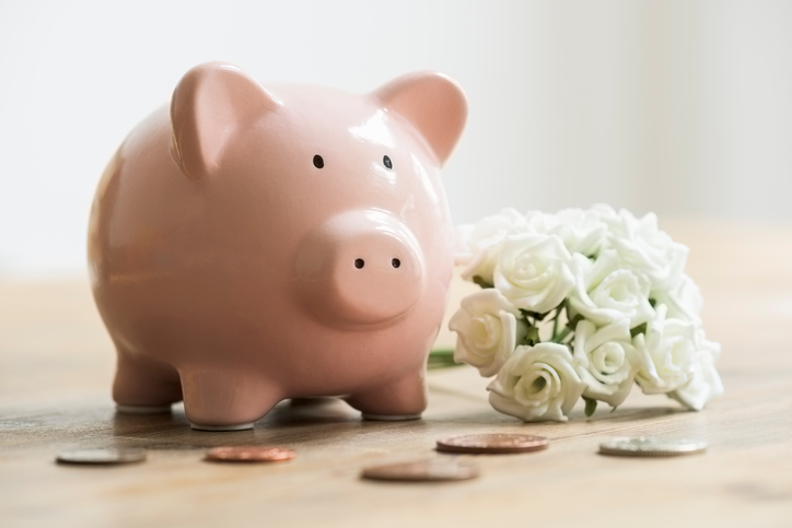 Wedding bouquet beside piggy bank and coins for saving